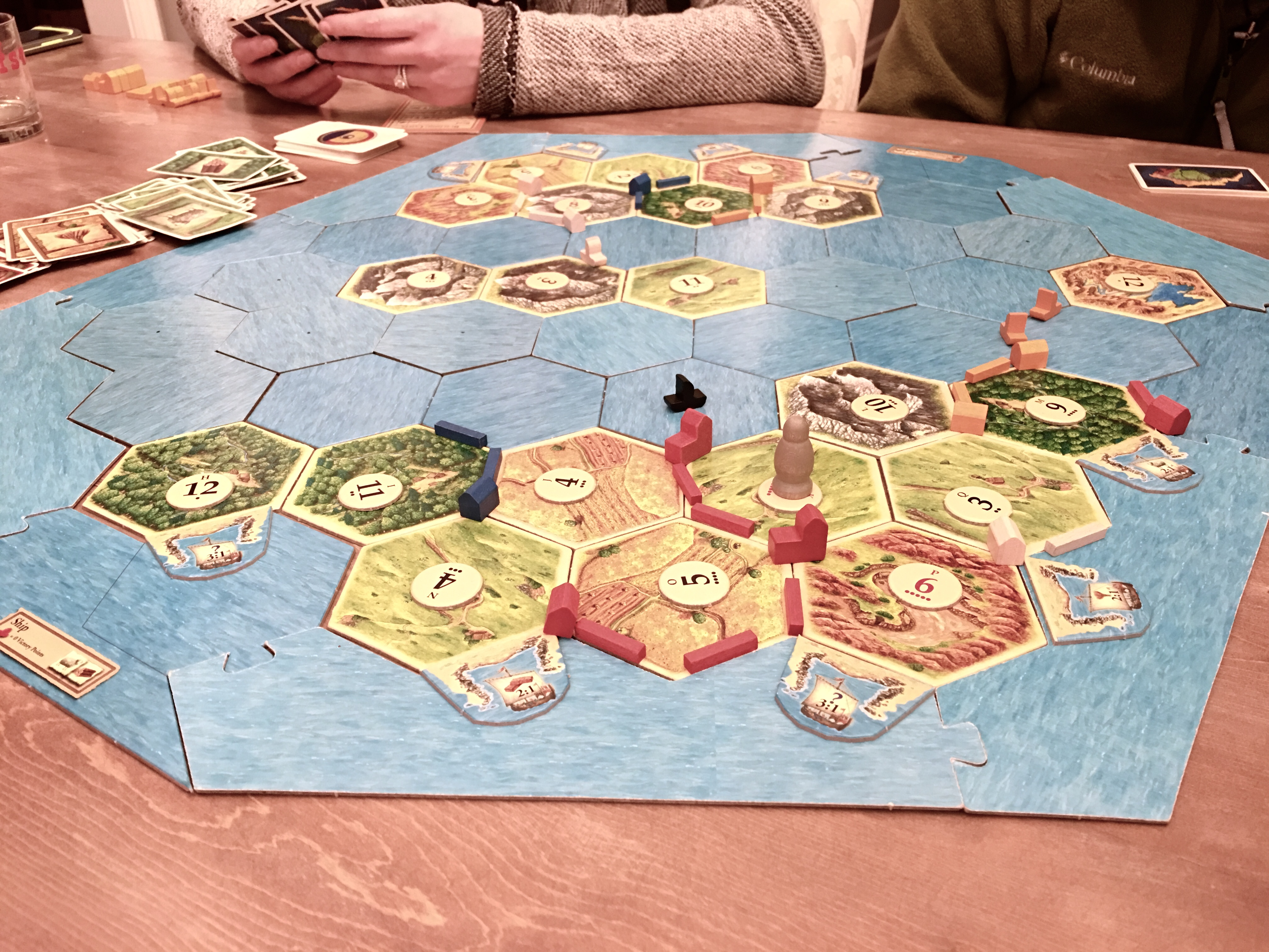close up photo of playing settlers of catan on farmhouse table
